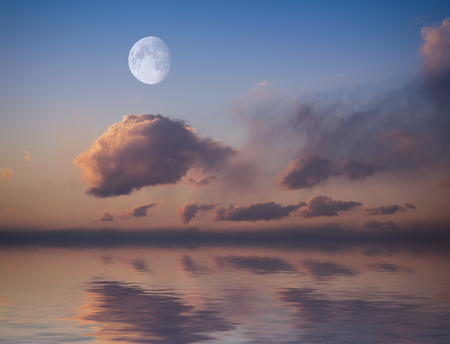 reflected: Moon with sunset sky reflected in water surface. Stock Photo