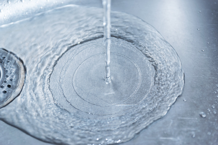stainles steel: Water flowing down the hole in a kitchen sink. Selective focus. Blue toned.