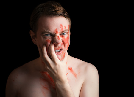merciless: Portrait of angry young man with paint on his face on dark background. Stock Photo