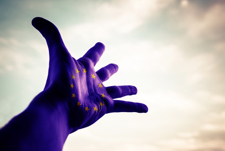 skepticism: Hand with European Union Flag with Great Britain in the sky. Conceptual image. Stock Photo