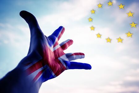 Hand with Great Britain Flag and European Union Flag in the sky. Conceptual image. Stock Photo