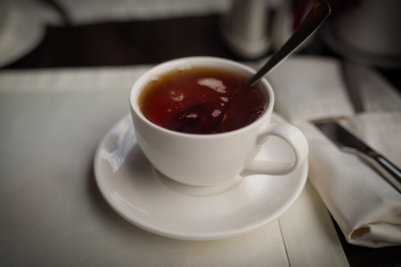 stimulated: Cup of black tea on a table in a cafe. Selective focus.