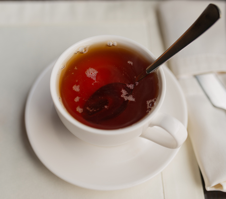 sooth: Cup of black tea on a table in a cafe. Selective focus.