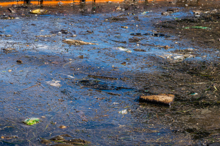 liquid state: Oil and garbage pollution in the water. Selective focus with shallow depth of field.