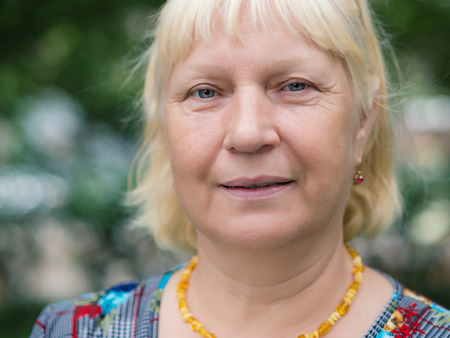 Portrait of beautiful aged woman in the park. Selective soft focus on eyes.