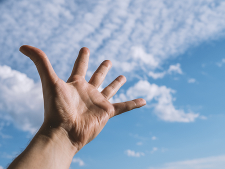 Hand of a man reaching to towards sky. Color toned image. Selective focus.