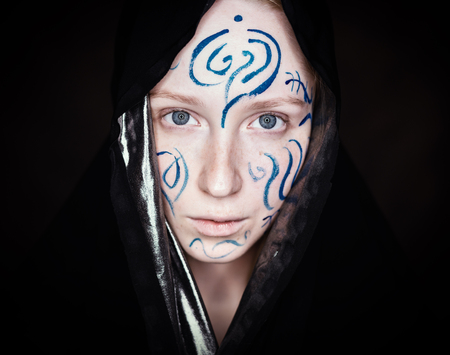 merciless: Portrait of young woman with paint on her face on dark background.