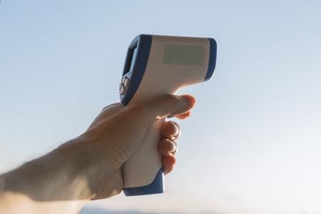 Ręka trzymaj bezdotykowy termometr na podczerwień na tle nieba. Selektywna ostrość.