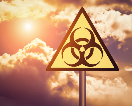 Yellow biohazard warning sign on against cloudy sky with sun.