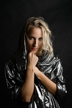 Portrait of beautiful woman in cape on dark background.