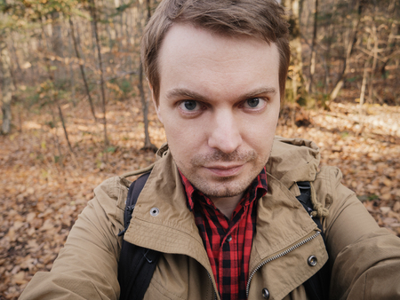 Young man makes selfie in the forest. Фото со стока