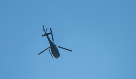 Flying helicopter in the blu sky.
