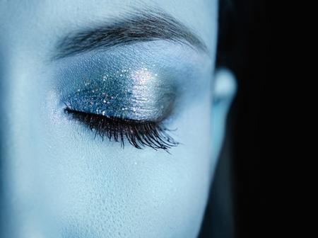 Beautiful female eye with blue make-up.