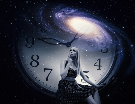 Young woman dressed in a dress with giant clock and galaxy. Time concept. Фото со стока