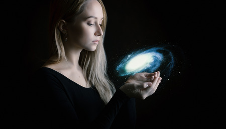Young woman holds galaxy in hands. Фото со стока
