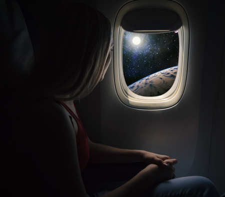 Woman in spaceship looks out the porthole. Commercial space travel concept. Фото со стока