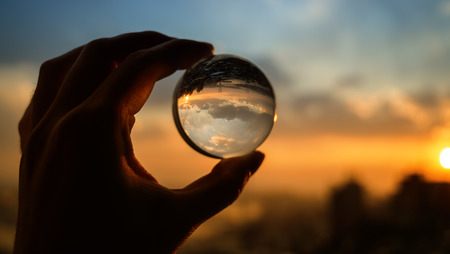 The hand holds glass ball which reflects sunset sky over city.