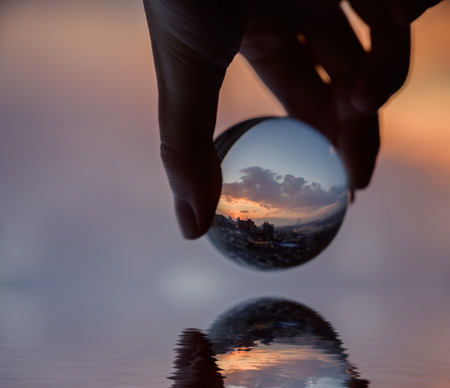 Hand holds glass ball which reflects sunset sky over city. Фото со стока