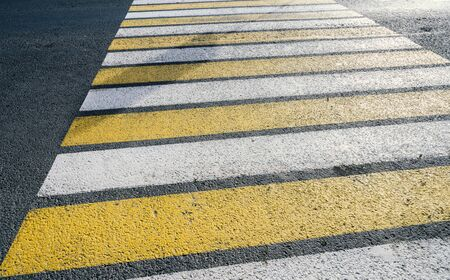 Detail of a yellow crosswalk on the road. Stock Photo