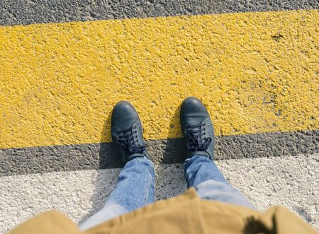 Top view of boots on the crosswalk.