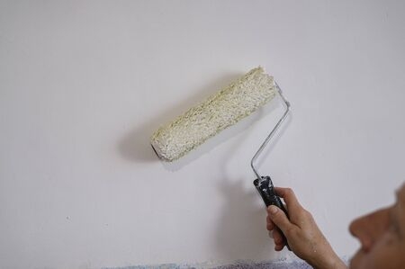 Authentic photo of aged woman painting interior wall with white paint. Imagens