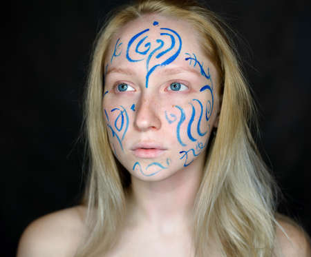 Portrait of young woman with paint on her face. 写真素材