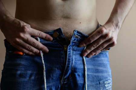 Man takes off his jeans. Selective focus.