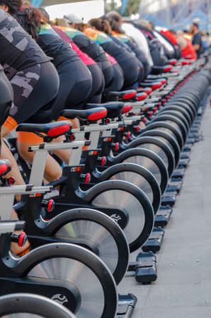 Row of bicycles with sportmen pedaling at an outdoor sporting event Reklamní fotografie