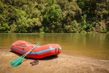 Inflatable boat adventure river raft ready for launch on the shore of a mountain stream