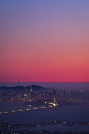 San Francisco city skyline at sunset as seen from across the bay with pink sky