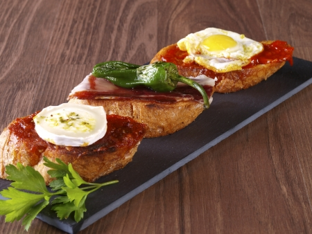 cured ham: Set of three different montaditos  Montadito is an appetizer or snack  Spanish Tapa  made with a slice of bread with some other food on it
