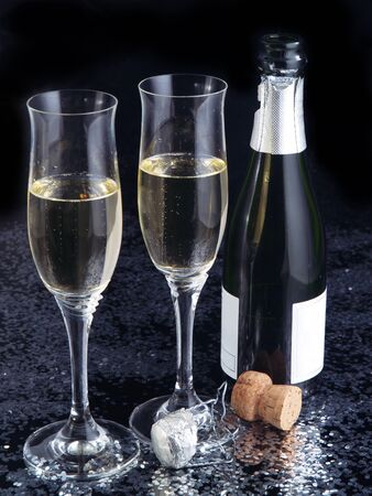 Two champagne flutes and a bottle on a black glossy background. photo