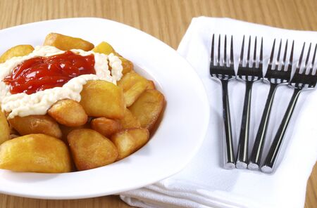 Patatas Bravas,  Fried potatoes served with mayonnaise and a hot spicy sauce  Spanish Tapa  Tapas are typical spanish appetizer  photo