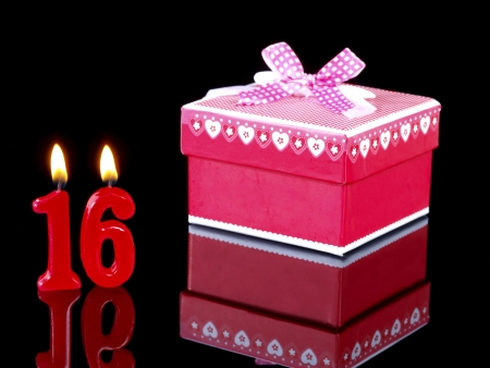 number 16: Birthday-anniversary gift with red candles showing Nr. 16 Stock Photo