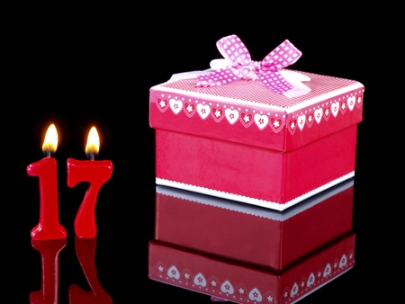 17: Birthday-anniversary gift with red candles showing Nr. 17 Stock Photo