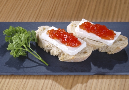 spanish tapas: Fresh cheese & tomato marmalade tapas  Spanish Tapa made with a slice of bread, fresh cheese and tomato marmalade. This kind of tapas served on a slice of bread are also called montaditos.