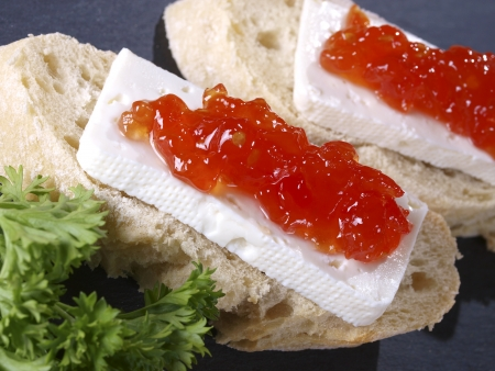 Fresh cheese & tomato marmalade tapas  Spanish Tapa made with a slice of bread, fresh cheese and tomato marmalade. This kind of tapas served on a slice of bread are also called montaditos.