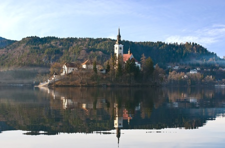 karawanks: The Assumption church located on a small island covered by light haze and surrounded by Karawanks, Slovenia
