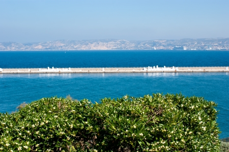The view on Marseille harbour with breakwater and mountains in light morning haze. photo