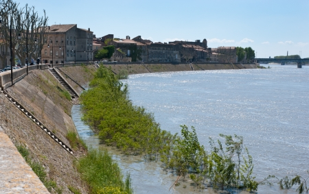 rhone: The left bank of Rhone river with the medieval houses, Arles, France Stock Photo