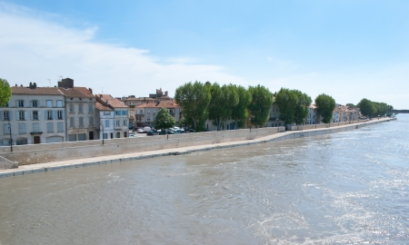 arles: The old houses of Arles  stay calm and look at Rhone river that flows fast because is always in a hurry. Stock Photo