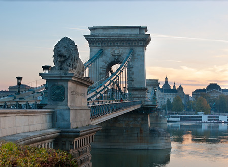 The Szechenyi Chain Bridge is decorated with sculptures of four lions, that guard the entrance to the bridge on both banks of Danube river, Budapest, Hungary.