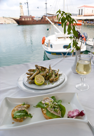 The romantic supper in the small cafe with local cuisine, consisting of seafood, Old Venetian Port of Rethymno, Crete, Greece  Stock Photo