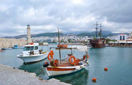 The fishing boats in the Old Venetian Port of Rethymno with the replica medieval warship on the background, Crete, Greece  photo
