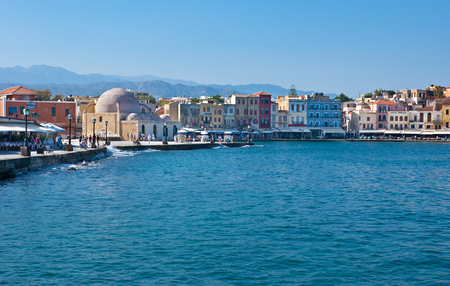 neighbouring: CHANIA, GREECE - OCTOBER 14, 2013: The colorfull cafes and restaurants of Venetian port are neighbouring with Hasan Pasha Mosque, on October 14 in Chania.