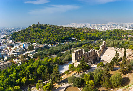 The view on the Odeon of Herodes Atticus - a stone theatre, located on the slope of Acropolis with the Philopappos Hill on the background, Athens, Greece. photo