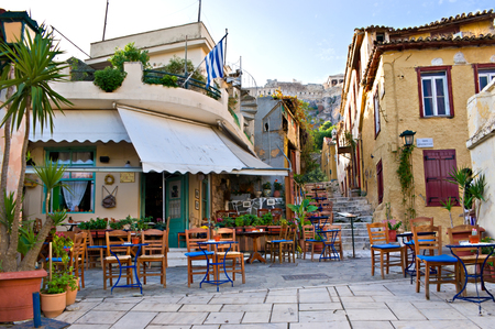 Athens, GREECE - OCTOBER 12, 2013: The old greek cafe surrounded by tiny tables in the yard, with a view on Acropolis on the top of the hill, on October 12 in Athens.