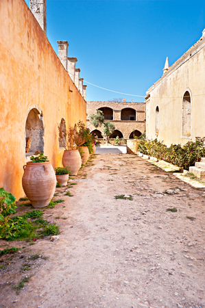 The courtyard of Arkadi Monastery with different flowers in amphoras, Crete. photo