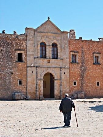 ida: RETHYMNO, GREECE - OCTOBER 15, 2013: The old man with a cane goes to the entrance (Western Door) of Arkadi Monastery, also called Rethemniotiki or Haniotiki, on October 15 in Rethymno.