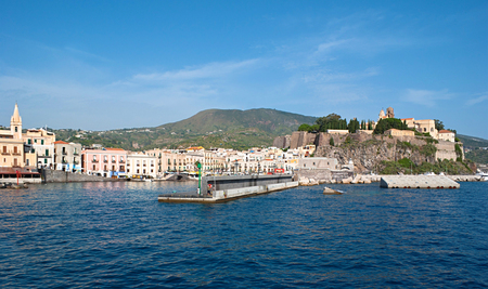 lipari: The yacht approaches the port of Marina Corta with the fortress Castello, that defends the harbour since medieval period, Lipari Island, Italy.